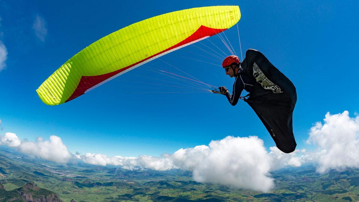 A paraglider pilot above hills and puffy clouds