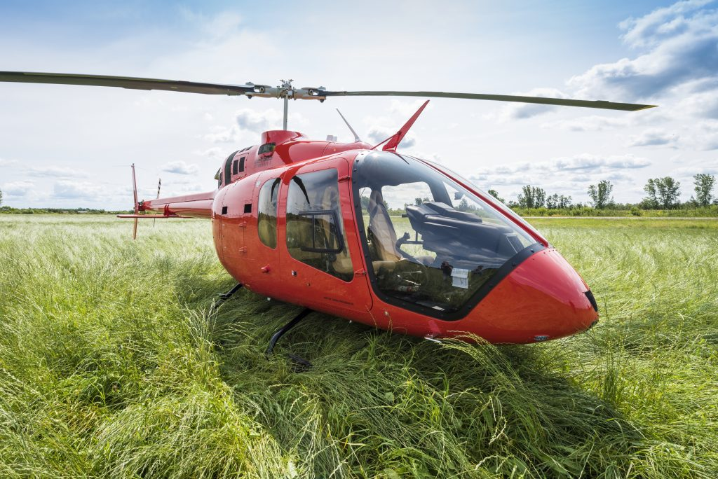 A Bell 505 helicopter sits ready to fly in the tall grass of a Colorado meadow