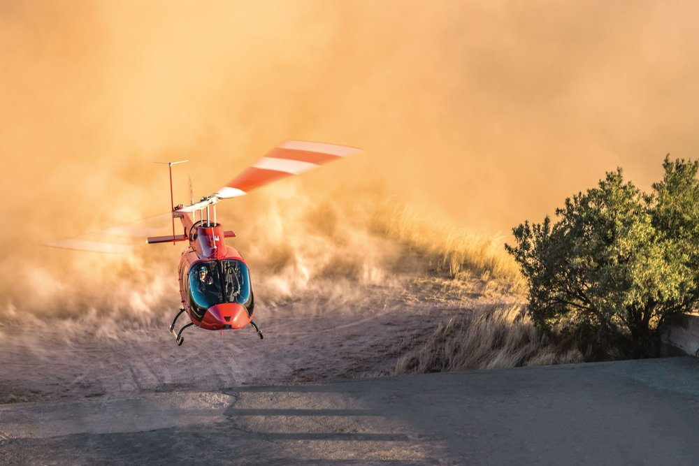 A Bell 505 Jetranger X swoops over a dusty landscape, its downwash swirling the sand up in its wake